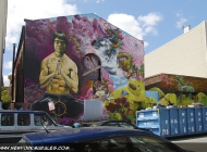 Here the wall, where there is a man, maybe Bruce Lee or Jackie Chan, meditating. The background is surrealistic, with dragon, turtle, a river,a cat, some birds and purple clouds covering the sky | Bruce Lee or Jackie Chan? | New York Murales