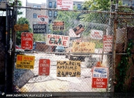 An iron gate covered with road signs and warnings (East Side) New York Murales
